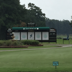 A long distance shot of a golf course and scoreboard