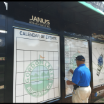 A man in a blue shirt keeps score on a golf score board