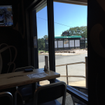 Inside a restaurant looking out at a golf scoreboard with black paint and green awning