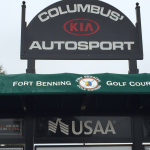 A close up picture of a black advertisement board, green awning over a golf scoreboard.