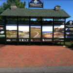 A golf course scoreboard with green tile roof and five panel advertisements