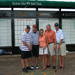 men and women stand in front of a golf scoreboard