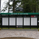 A black and white golf scoreboard with green overhang
