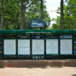 a brick pathway leads up to a golf scoreboard with advertising