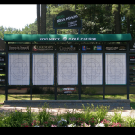 A golf scoreboard behind an area of landscaping on a golf course